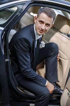 Beau marié sortant d'une voiture