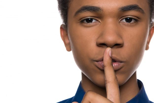 Beau mec africain met son doigt sur sa bouche