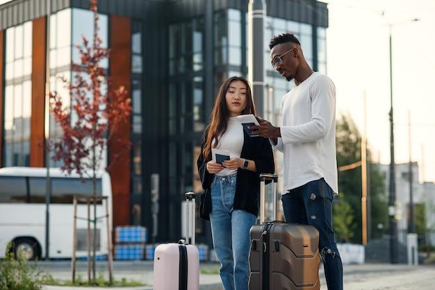 Beau mec afro-américain barbu et jolie fille asiatique se rassemblant en voyage d'affaires avec des valises en attente à l'arrêt.