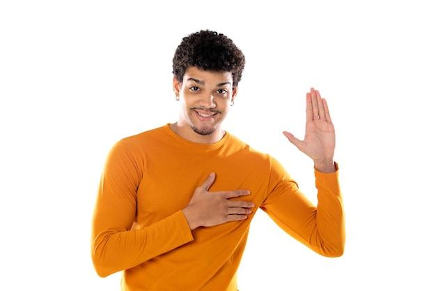 Beau mec afro avec sa main droite sur le coeur isolé