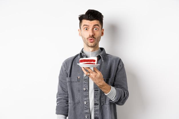 Beau mec d'anniversaire soufflant la bougie sur le gâteau et faisant le souhait, à la recherche idiot à la caméra, debout sur fond blanc.