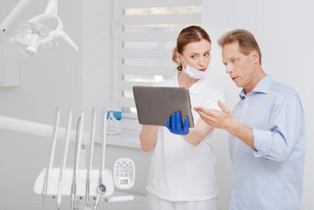 Beau mec attentif concerné ayant une consultation au bureau du dentiste et discutant du traitement pendant qu'elle démontre les résultats de ses tests sur tablette