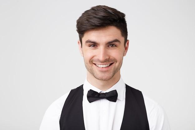 Beau mec attrayant intelligemment habillé avec un nœud papillon noir attrayant regardant directement la caméra avec un large sourire joyeux, a l'air heureux satisfait, isolé sur un mur blanc