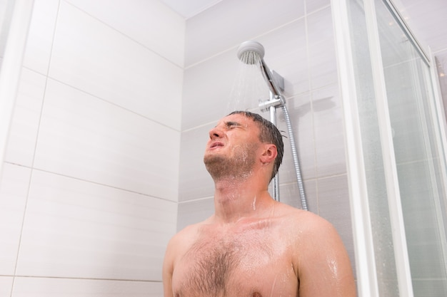 Beau mec aux yeux fermés debout sous l'eau qui coule dans la cabine de douche avec portes en verre transparent dans la salle de bains carrelée moderne