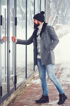 Beau mec barbu entre dans le bâtiment. homme fashion dans un manteau d'hiver à l'extérieur.