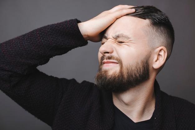 Beau mec barbu grimaçant et giflant le front avec la main en se tenant debout sur fond gris