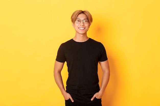 Beau mec blond asiatique dans des verres debout dans des vêtements noirs et souriant heureux, mur jaune