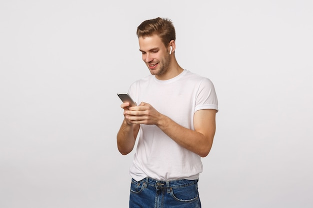 Beau mec blond aux yeux bleus et t-shirt blanc à l'aide de smartphone