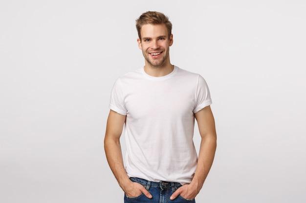 Beau mec blond aux yeux bleus et t-shirt blanc posant