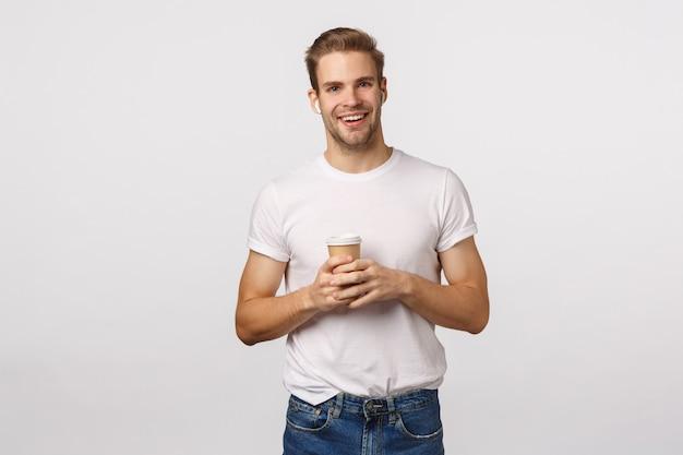 Beau mec blond aux yeux bleus et t-shirt blanc tenant une tasse de café en papier