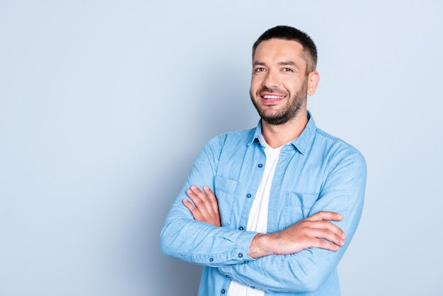 Beau mec avec une chemise bleue posant contre le mur bleu clair
