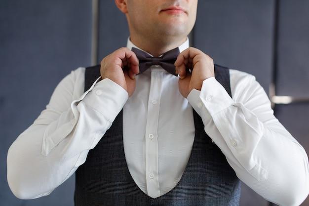 Beau mec en costume gris et nœud papillon en gros plan le jour du mariage dans la chambre d'hôtel sur fond