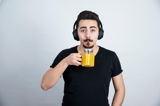 Beau mec dans les écouteurs buvant dans une tasse en verre avec du jus d'orange.