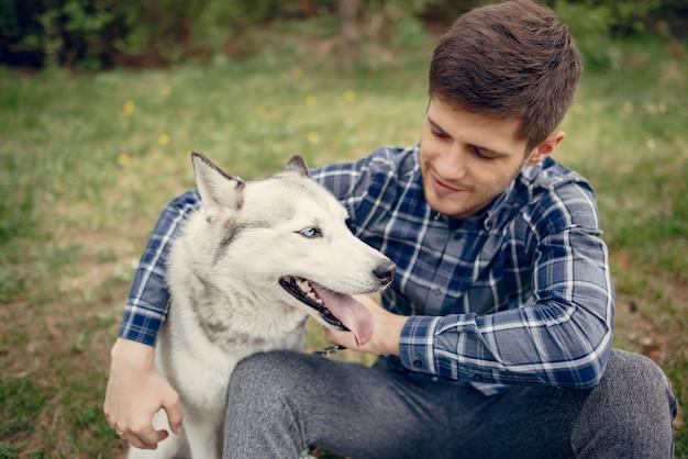 Beau mec dans un parc d'été avec un chien