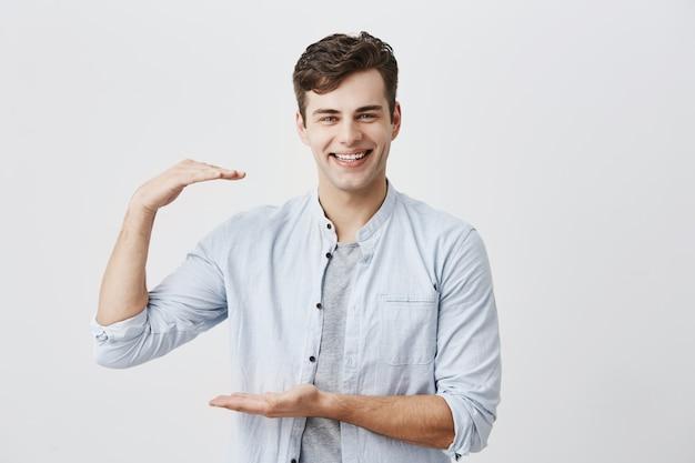Beau mec élégant portant une chemise bleue sur un t-shirt montrant la taille de quelque chose de petit avec les mains, gesticulant, souriant largement avec des dents blanches. homme aux cheveux noirs posant