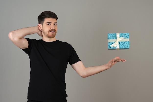 Beau mec essayant d'attraper le cadeau et regardant la caméra.