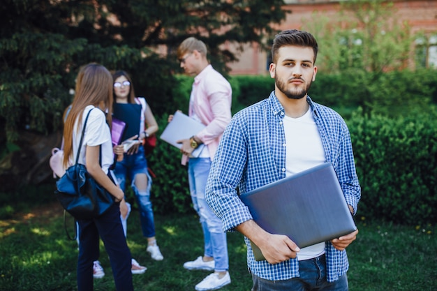 Beau mec étudiant sur le campus. tient un ordinateur portable entre vos mains. bonne journée.
