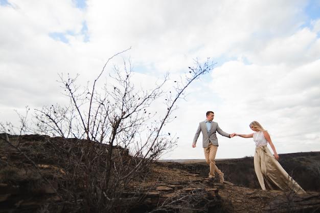 Beau mec et fille blonde marchant sur le terrain, un homme mène une femme tenant la main.