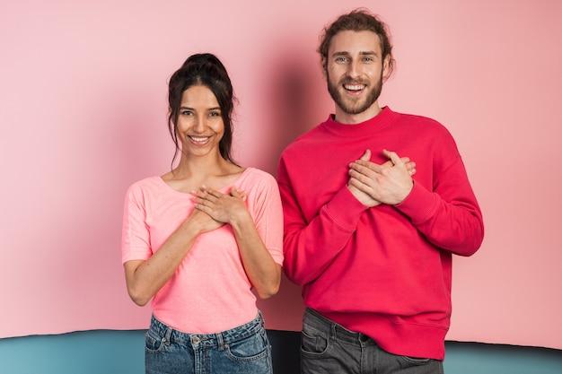 Beau mec et fille touchant leur poitrine avec leurs mains, montrant un geste du cœur.
