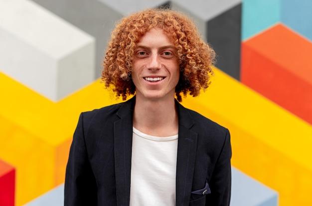 Beau mec gingembre millénaire souriant avec des cheveux bouclés portant une tenue de style décontracté chic à la recherche en se tenant debout contre un mur géométrique coloré