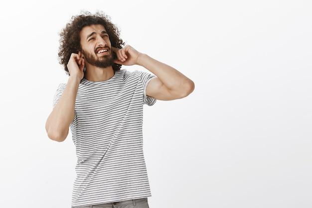 Beau mec hispanique dérangé avec une coiffure afro, regardant le coin supérieur droit avec une expression dégoûtée ennuyée, couvrant les oreilles avec l'index, fronçant les sourcils de mécontentement