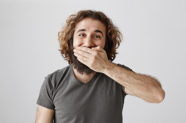 Beau mec idiot du moyen-orient avec la bouche, souriant ou riant heureux