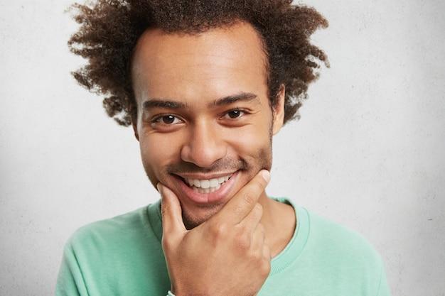 Beau mec insouciant avec une expression joyeuse, sourit largement, montre des dents blanches même