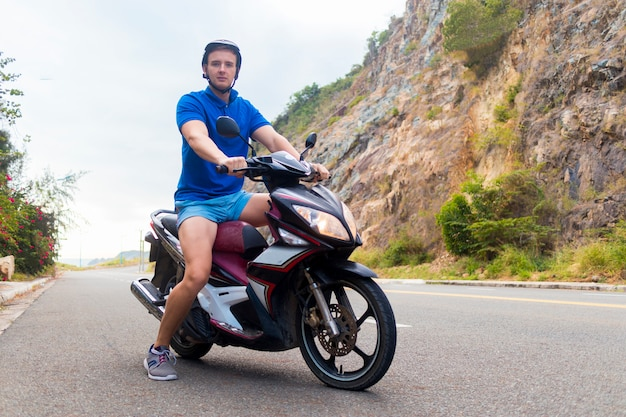 Beau mec, jeune homme, motard ou motocycliste est à cheval, conduisant une moto, un cyclomoteur ou un vélo. cavalier en casque sur la route dans les montagnes dans une journée d'été en asie, vietnam