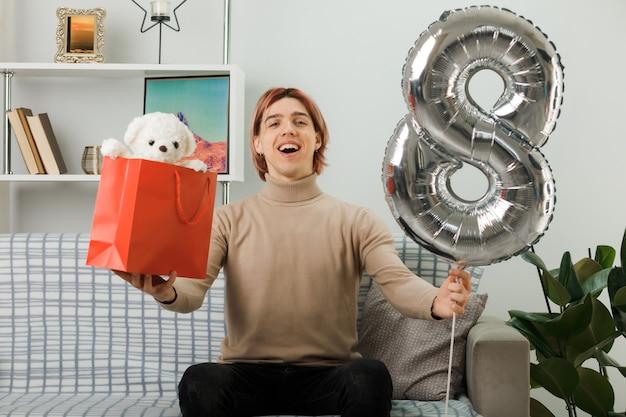 Beau mec le jour de la femme heureuse tenant un ballon numéro huit avec un sac-cadeau assis sur un canapé dans le salon