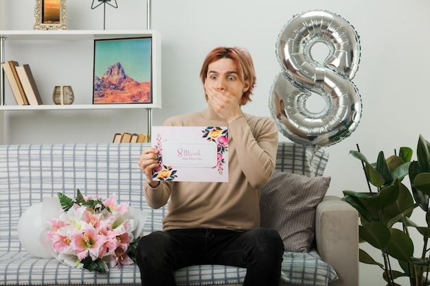 Beau mec le jour de la femme heureuse tenant une carte postale assis sur un canapé dans le salon