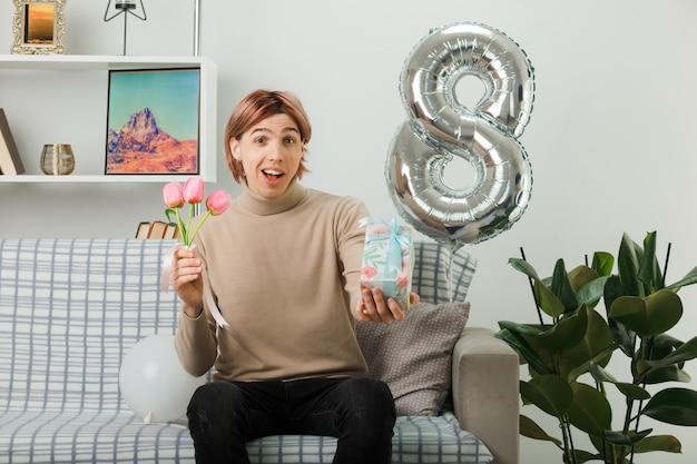Beau mec le jour de la femme heureuse tenant des fleurs avec présent assis sur un canapé dans le salon
