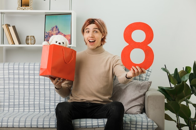 Beau mec le jour de la femme heureuse tenant le numéro huit avec un sac-cadeau assis sur un canapé dans le salon