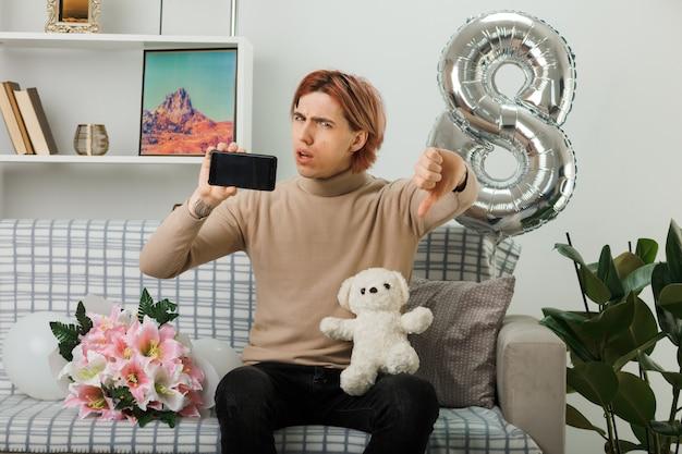 Beau mec le jour de la femme heureuse tenant un ours en peluche avec un téléphone assis sur un canapé dans le salon