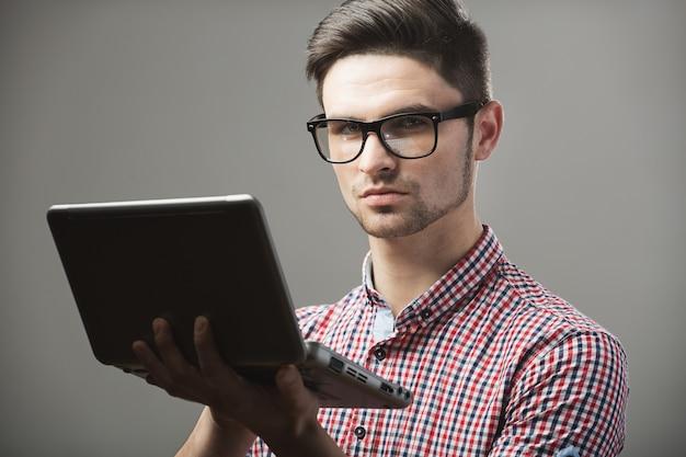 Beau mec avec des lunettes et un ordinateur portable