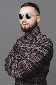Beau mec en lunettes de soleil élégantes et chemise à carreaux gardant les bras croisés et regardant la caméra en se tenant debout sur fond gris