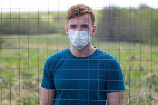 Beau mec en masque de protection sur son visage isolé debout derrière les barreaux, treillis. restriction de liberté. auto-isolement en raison d'une infection par le virus épidémique du coronavirus. covid19. jeune homme isolé