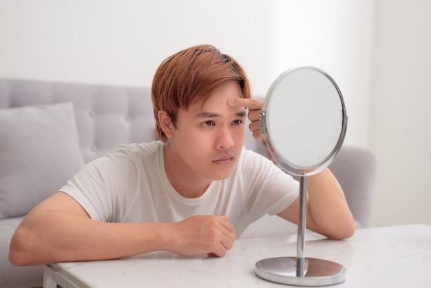 Beau mec millénaire frustré préoccupé par un problème de peau du visage