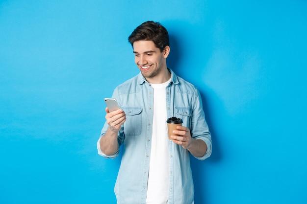 Beau mec moderne lisant un message sur téléphone portable et buvant du café, debout sur fond bleu.