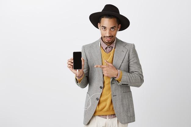 Beau mec noir impertinent en costume et chapeau hipster, écouter de la musique dans les écouteurs, pointer du doigt sur l'écran du smartphone