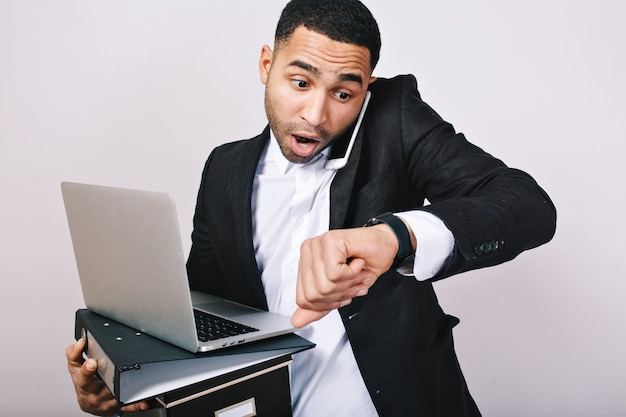 Beau mec occupé en chemise blanche et veste noire parlant au téléphone, tenant des dossiers, un ordinateur portable, a l'air étonné de regarder. être en retard, réunion, employé de bureau, carrière.