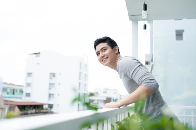 Beau mec relaxant sur un balcon, isolé sur fond de ville