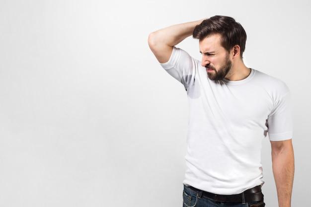 Beau mec renifle son aisselle. il y a une grosse tache de sueur et le gars ne l'aime pas du tout et rétrécit. il n'aime pas son odeur. isolé sur mur blanc.