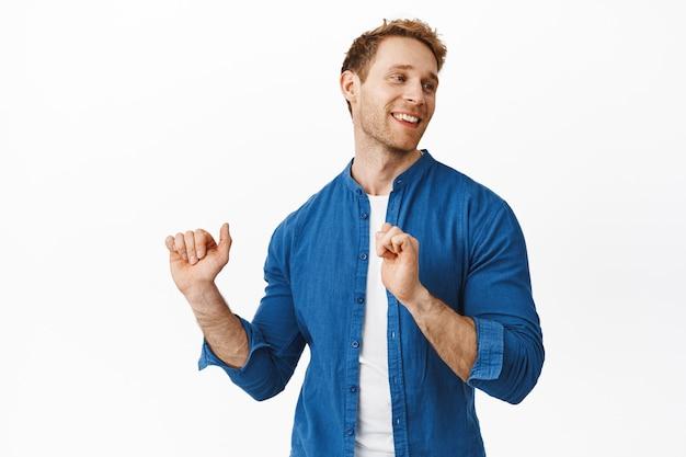 Beau mec roux élégant dansant, s'amusant et souriant, se relaxant sur la piste de danse, regardant de côté avec un visage froid et satisfait, debout sur un mur blanc