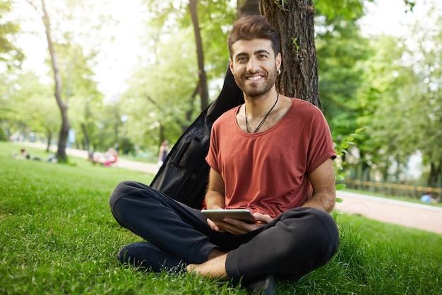 Beau mec se penche sur l'arbre, lisant un livre électronique avec une tablette numérique dans le parc