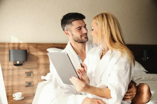 Le beau mec a son amante sur ses genoux et la serre doucement dans ses bras paiement en ligne dîner en ligne et réservation de spa