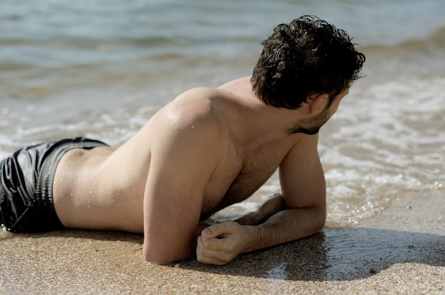 Beau mec topless sexy allongé dans l'eau de mer, pas de visage