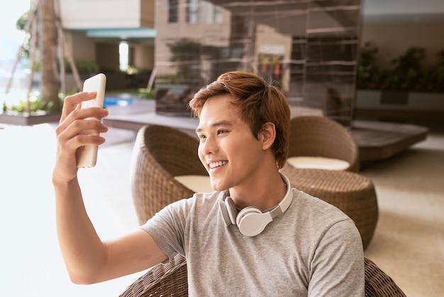 Beau mec utilisant un téléphone portable par une journée d'été ensoleillée