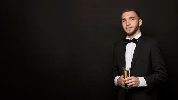 Beau mec en veste avec un verre de boisson