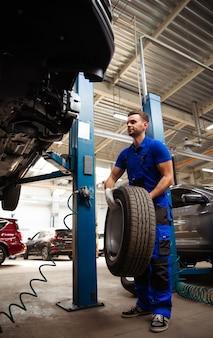 Un beau mécanicien automobile professionnel change une roue sur une voiture ou effectue un changement de pneu dans un centre de réparation automobile spécialisé