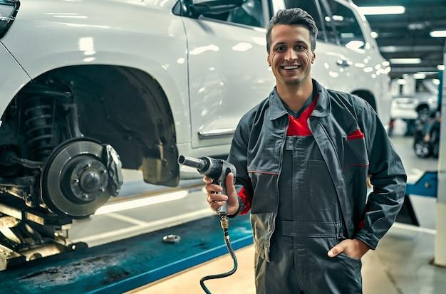 Un beau mécanicien en uniforme travaille dans le service automobile. réparation et entretien de voitures. boulons de torsion/dévrillage sur la roue.